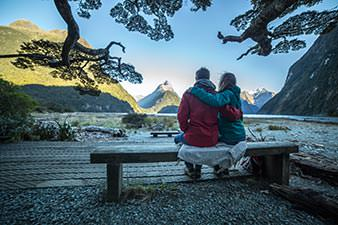 Couple with their arms around each other looking out across Milford Sound